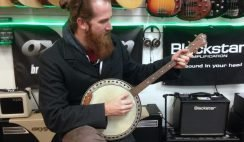 A man playing Banjo with some sound equipment and guitars in the background